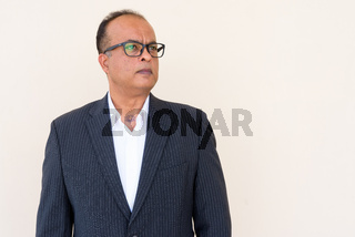 Portrait of Indian businessman thinking against plain wall outdoors