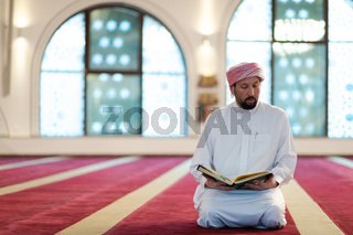 muslim man praying Allah alone inside the mosque and reading islamic holly book