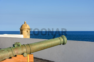 Old iron cannon and guardhouse on the walls of the historic fortress of Farol da Barra