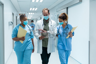 Diverse group of male and female doctors wearing face masks walking looking at tablet