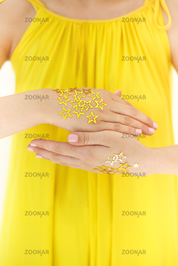 Crop woman with golden decorative stars