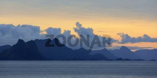 Sonnenaufgang mit Wolken hinter Bergen auf den Lofoten