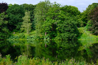 Beautiful landscape of trees foliage and the Fish Pond  in the area of the Harewood House Trust in West Yorkshire in the United Kingdom