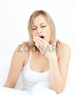 Exhausted woman yawning sitting on her bed