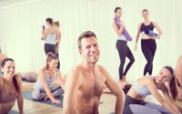 Portrait of a cheerful male hot yoga instructor relaxing after giving yoga class to large group of sporty attractive people. Healthy active lifestyle, working out indoors in gym.