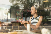 Thoughtful caucasian woman holding mobile phone while looking through the coffee shop window during coffee break.