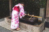 Woman in kimono rinsing hands at Japanese purify water fountainat Fushimi Inari shrine, Kyoto, Japan