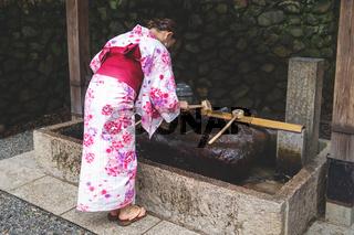 Woman in kimono rinsing hands at Japanese purify water fountain, called chozubachi, at Fushimi Inari shrine, Kyoto, Japan