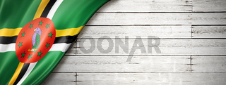 Dominica flag on old white wall banner
