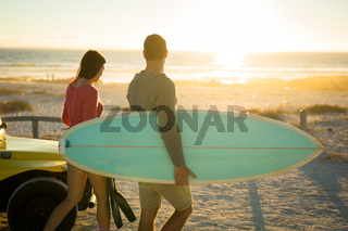 Caucasian couple on the beach carrying surfboard during sunset