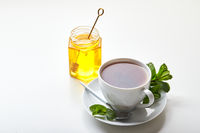 Black tea in white cup with mint leaves and honey. Calming and revitalizing tea, anti-stress and relaxation