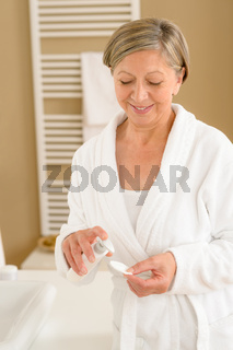 Senior woman bathroom apply face make-up removal
