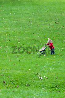 Kleines Mädchen schiebt Puppenwagen