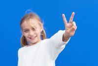 Young beautiful blond girl wearing casual sweater over blue background smiling looking to the camera showing fingers doing victory sign. number two.