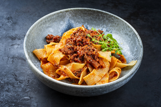 Modern style traditional Italian ragu alla bolognese sauce with papedelle pasta noodles and parmesan cheese served as close-up in a ceramic design bowl with copy space