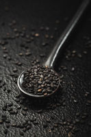 Black sesame seeds in small spoon on black background. Macro studio shot.