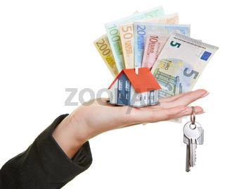 Hand hält Haus, Schlüssel und Geldscheine