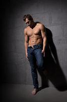 Sexy shirtless muscular man standing near wall