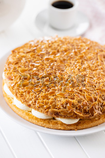 Sweet almond cake. Pie with cream and almonds on white table.