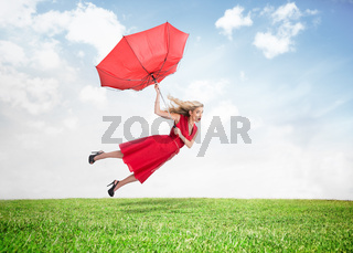 Beautiful woman flying above the grass