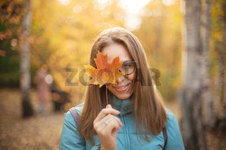 Beautiful autumn woman with autumn leaves
