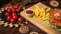 Tasty beef burger and french fries with a cherry tomatoes served on a decorative wooden part of a simple mechanism. Street food concept. Fast food concept. Restaurant concept
