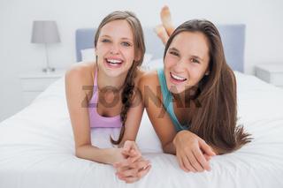 Friends lying in bed