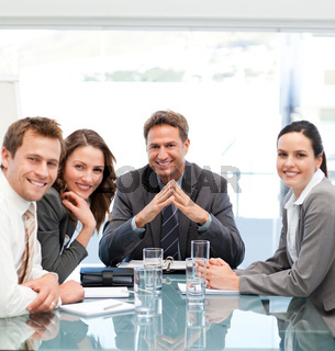 Portrait of a positive manager with his team sitting at a table