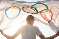 Blonde boy waving waving flag the Olympic Games outdoors over blue sky at the river bank