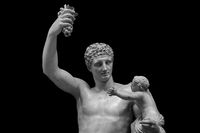 Statue of Dionysus or Bacchus with bunch of grapes isolated on black
