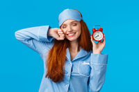 Girl slept well, wake up energized, sleepy stretching with closed eyes and lovely smile, holding red cute clock, set up alarm to be work in time, wearing pyjama and sleep mask, blue background