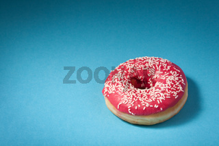 donut with red icing isolated on blue background with copyspace