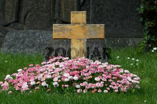 verwittertes Holzkreuz an einem Grab mit blühenden Frühlingsblumen