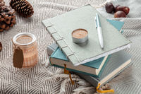 Hygge. Journals and scented candles on a warm blanket, lazy winter morning