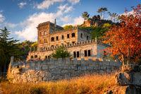 Abandoned ruin building of Termas Radium Hotel Serra da Pena in Sortelha with beautoful colorful trees at sunset, Portugal