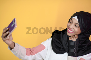 african muslim woman with a beautiful smile takes a selfie with a cell phone