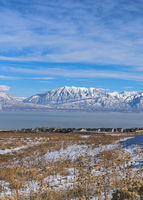 Vertical A panoramic view of the snowy wasatch mountains with the clear blue sky in the background