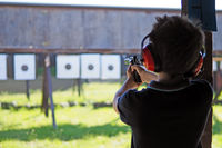 Young boy concentrates while shooting from a revolver at a shooting range