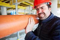 Handwerker auf der Baustelle transportiert ein Rohr