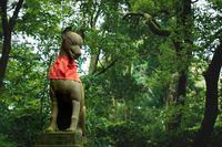 Fox kisune statue in forest at the Fushimi Inari Taisha shrine in Kyoto, Japan