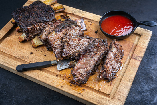 Traditional barbecue burnt chuck beef ribs marinated with spicy rub and served with a hot chili sauce as closeup on a rustic wooden cutting board