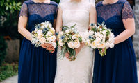 Bride and bridesmaids in identical blue dresses are standing side by side and holding bouquets in their hands, close-up