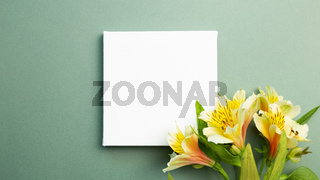 Empty white canvas with yellow flower bouquet on green background. top view, copy space