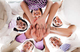 Smiling business people holding hands together in a circle