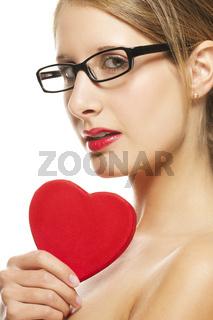 junge frau mit schwarzer brille hält herz