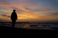 Silhouette of a vacationer walking on the beach in Kolobrzeg on the Polish Baltic coast after sunset