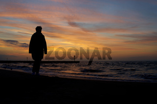 Silhouette einer Urlauberin beim Strandspaziergang in Kolobrzeg in Polen
