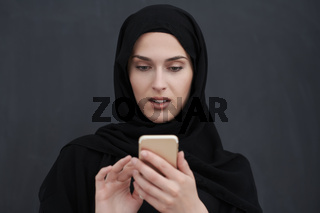 Young muslim businesswoman in traditional clothes or abaya using smartphone