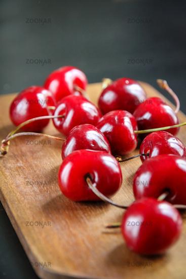 Fresh cherries on a wooden cutting board