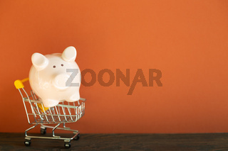 Pink piggy bank in shopping cart on wooden desk. red wall background